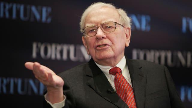 Buffett mit ausgestreckter Hand an einer Konferenz