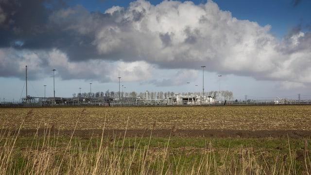 Ein grosses Feld mit einer Gasförderanlage am Horizont.