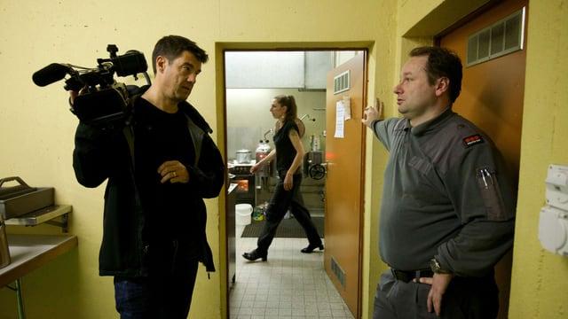 Fernand Melgar mit Kamera spricht mit einem Security-Mann. Im Hintergrund läuft eine Frau durch das Film.
