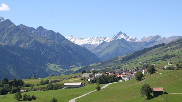 Dorf in einem weiten Bergtal.