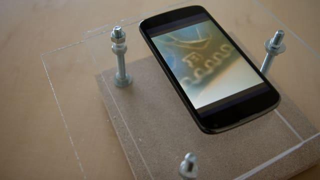 Handy auf Plexiglasplatte von einem Gestell gehalten.
