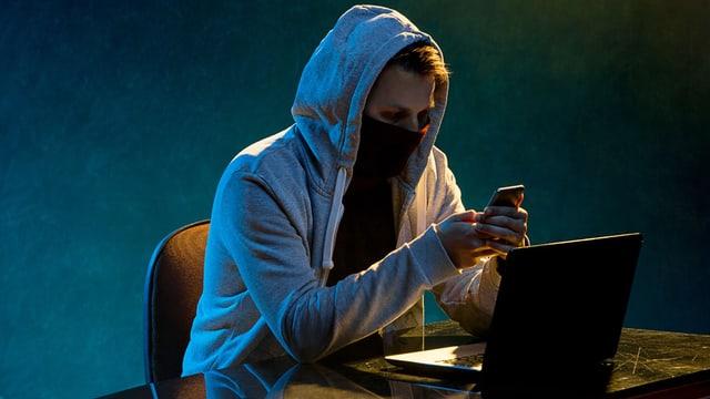 Maskierter Mann mit Handy.