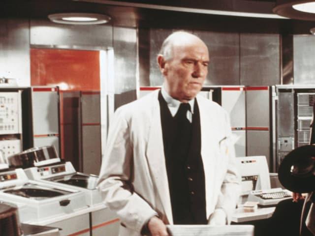 Ein Mann mit weissem Kittel steht vor diversen Computern.