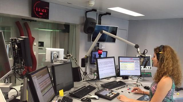 Auf dem Bild sieht man das Sendestudio von SRF 4 News in Bern, mit Moderatorin Miriam Knecht und den vielen Bildschirmen und Reglern für den Radio-Livebetrieb.