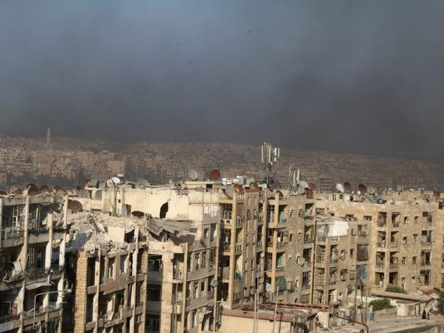 Stark beschädigte Häuserzeile, über der Stadt schwarzer Rauch.