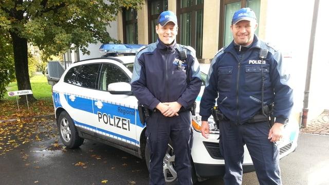 Zwei Polizisten der Repol Seetal stehen vor ihrem Einsatzfahrzeug.