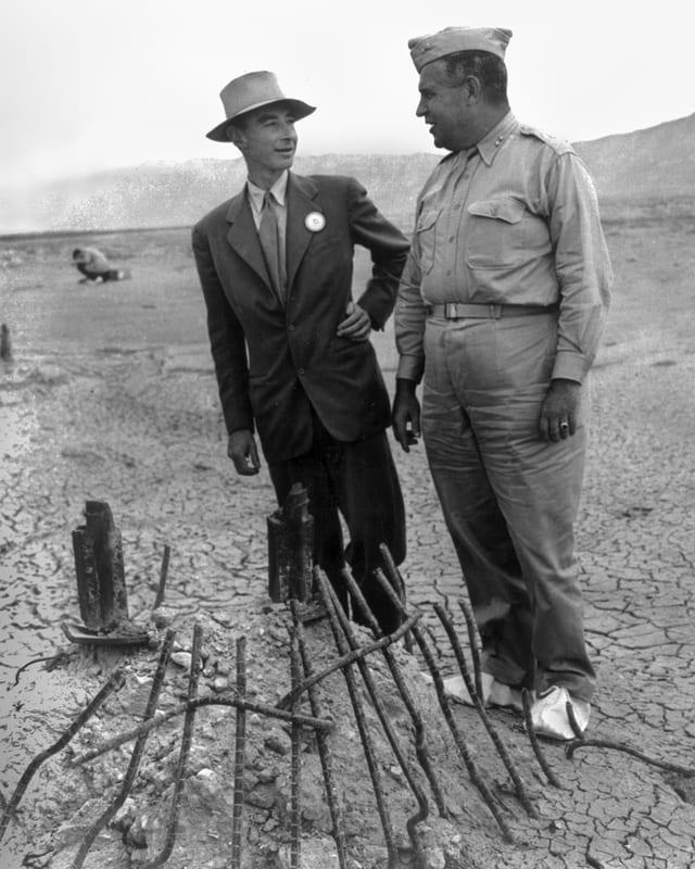 Oppenheimer im Anzug und mit Hut neben Groves in Uniform in einer Wüstenlandschaft