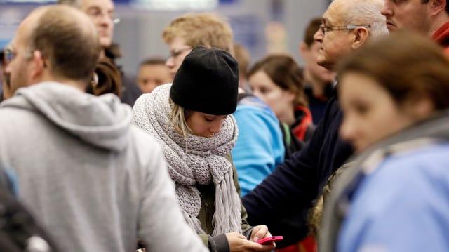 Frau starrt inmitten einer Menschenmenge auf ihr Telefon