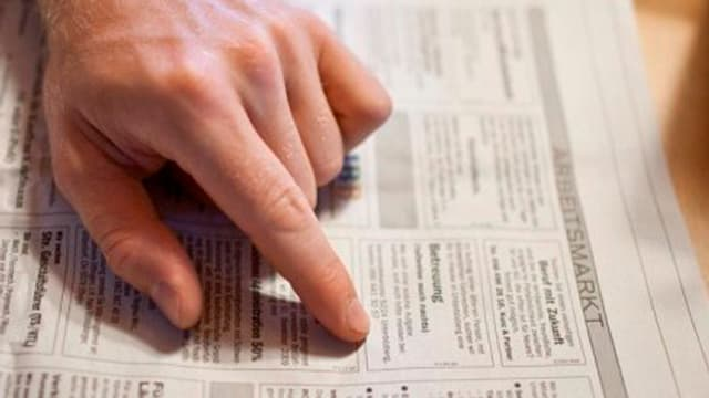 Eine Hand zeigt in einer Zeitung auf ein Stelleninserat.
