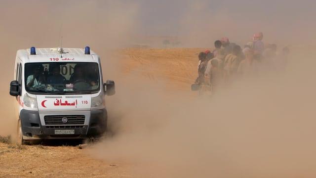 Eine Ambulanz fährt an einem Lastwagen voller Flüchtlinge vorbei, viel Sand wirbelt durch die Luft