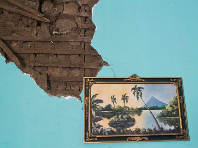Ein Gemälde einer Landschaft mit Palmen, Inseln und einem Berg hängt an einer beschädigten, hellblauen Wand.