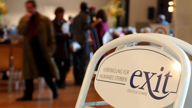 Ein Klappstuhl mit dem Exit-Logo, im Hintergrund eine Menschenansammlung.