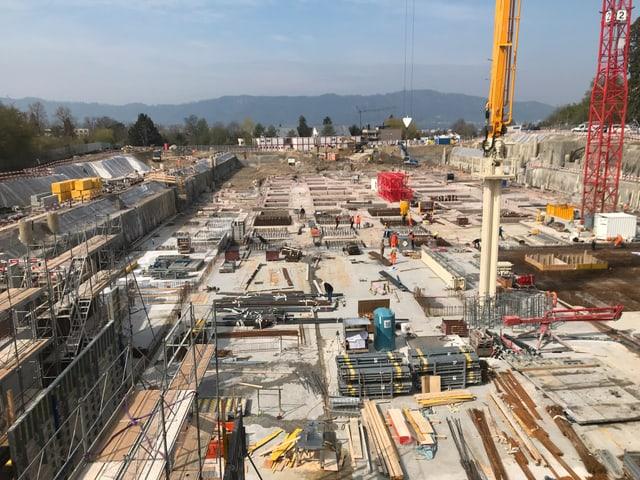 Blick in die Baugrube, in der gerade die Bodenplatte des Hauptgebäudes betoniert wird.