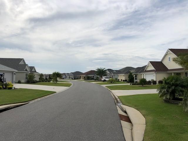Leere Strasse, von einheitlichen Einfamilienhäuser gesäumt.