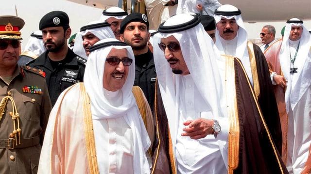 Symbolbild: Der saudische König Salman (rechts) empfängt den kuwaitischen Emir al Sabah auf dem Flughafen, im Hintergrund weitere Männer in arabischer Kleidung sowie Sicherheitsmänner..