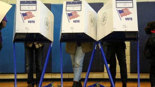 Drei US-Bürger stehen an den Wahlkabinen und geben ihre Stimme ab.