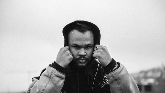 schwarzweiss bild des kapuzentragenden böse blickenden rappers