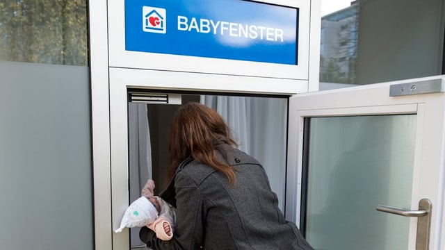 Eine Frau legt eine Pupe ins Babyfenster.