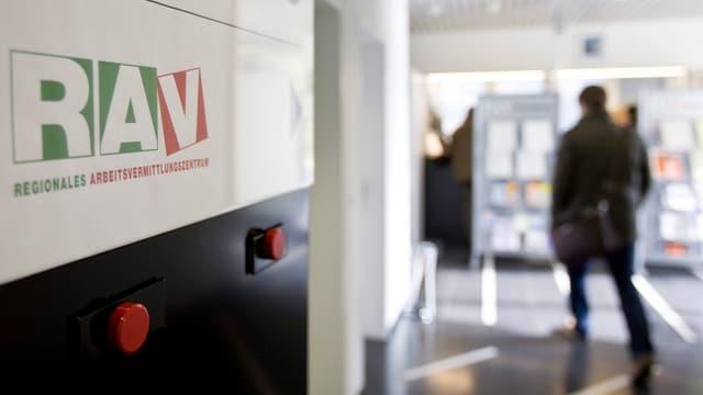 Eingang zu einem RAV mit dem Logo links an der Wand, rechts von hinten ein Klient.