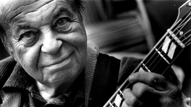 Schwarzweissfoto eines Mannes mit Gitarre.