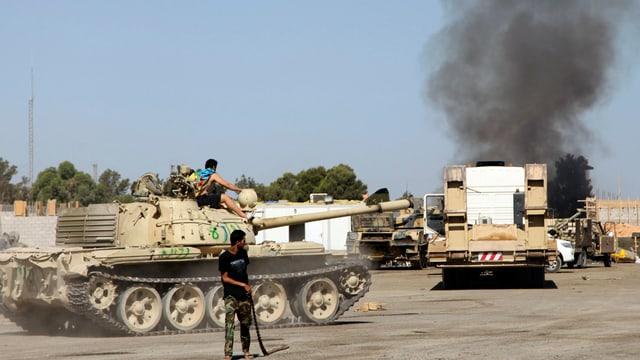 Ein Mann vor einem Panzer, im Hintergrund steigt Rauch auf.