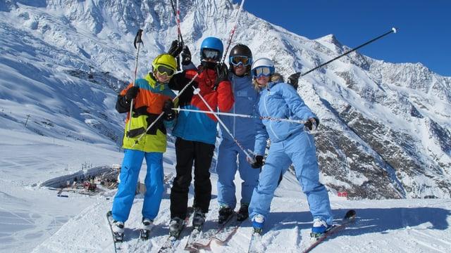Eine Gruppe Skifahrer steht auf einer Schanze.