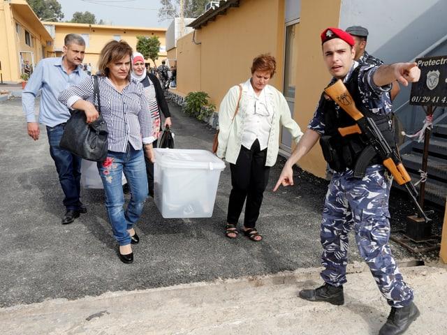 Personen tragen eine Wahlurne aus dem Wahllokal.