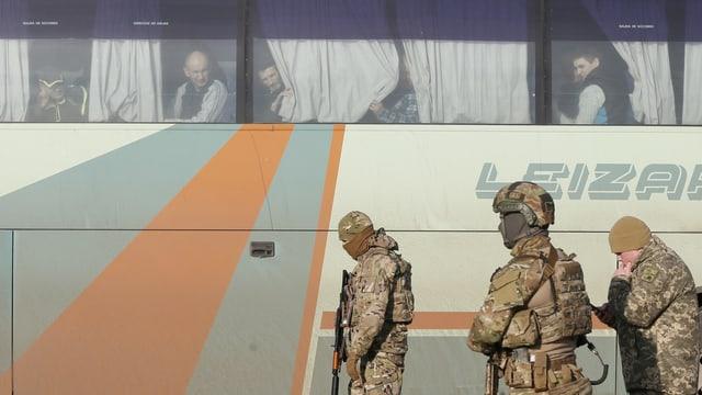 Gefangene in einem Bus, davor patroullieren Soldaten.