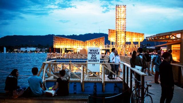Ein paar Menschen sitzen vor dem Eingang der Ausstellung «What People Do For Money» an der Manifesta Zürich.