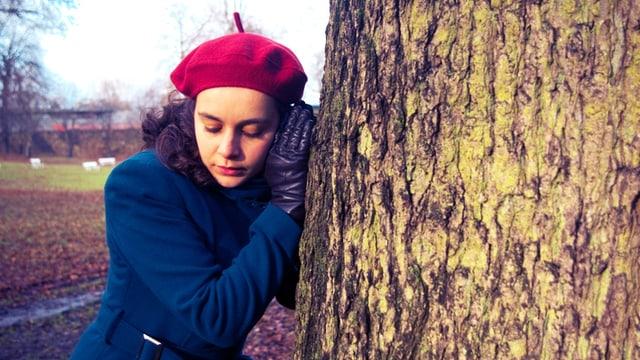 Eine Frau mit Mütze und Mantel hält ihr Ohr an einen Baumstamm.
