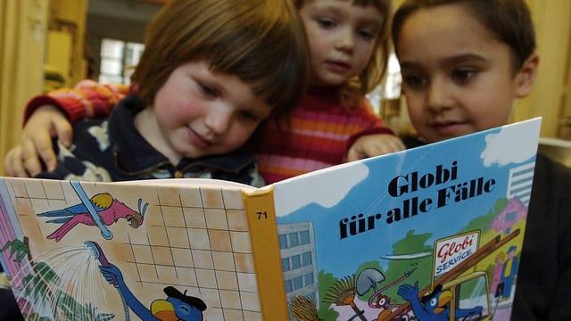 Kinder schauen ein «Globi»-Buch an.