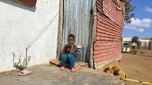 Ein Mädchen sitzt vor einem Haus