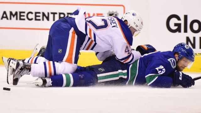 Ein Spieler von den Edomnton Oliers liegt über einem Spieler der Vancouver Canucks.