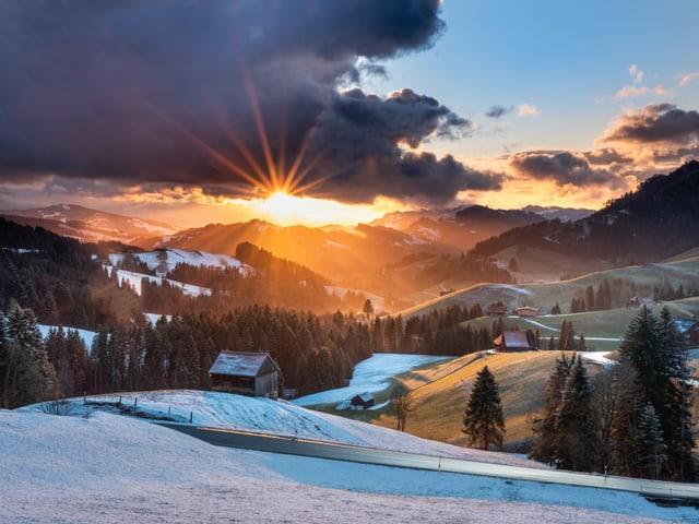 Sonnenuntergang hinter einer hügeligen Schneelandschaft.