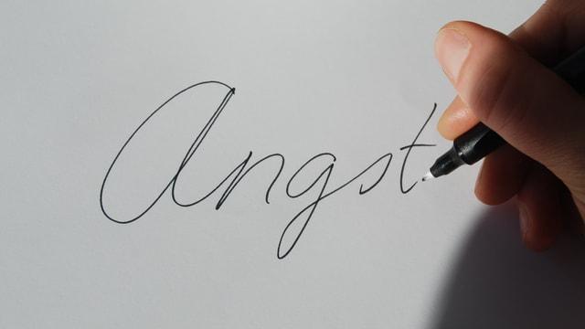 Zu sehen ist eine Frauenhand, die mit einem Stift das Wort Angst auf ein Blatt Papier schreibt.