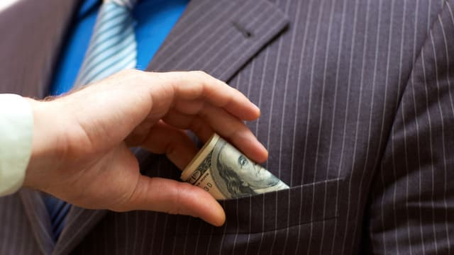 Eine Person steckt einem Mann ein Bündel Geldnoten in die Jackentasche.