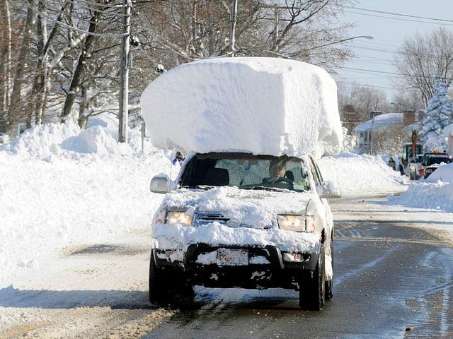 Auto mit viel Schnee auf dem Dach