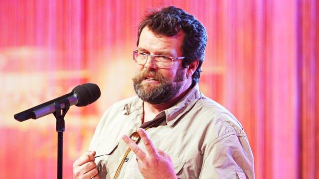 Jochen Malmsheimer auf der Bühne. Er steht neben einem Mikrofon und trägt ein beiges Hemd und eine Brille.