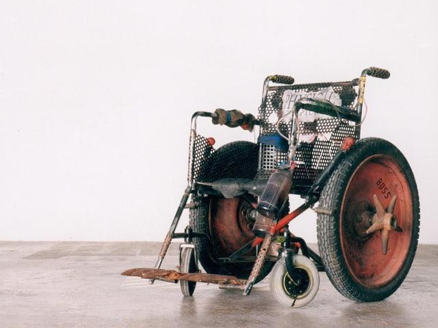 Metallener Rollstuhl mit Traktorenrädern, an dem unter anderem eine Flasche befestigt ist.