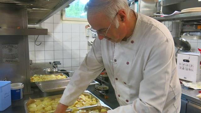 Ein Koch steht in einer grossen Küche am Herd.