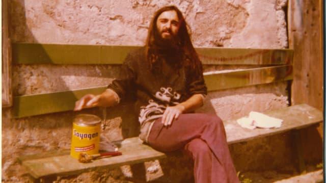 Ein Mann mit langen Haaren und Vollbart sitzt auf einer Bank.