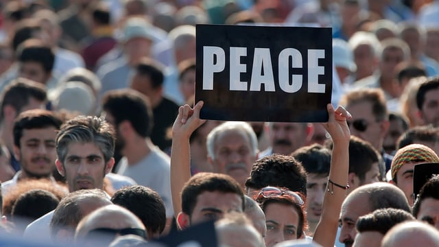 Demonstrant hält Schild mit Schriftzug «Peace» hoch