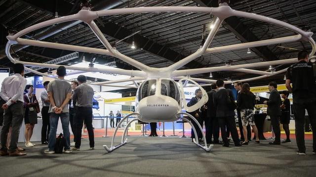 Menschen stehen um ein modernes Air Taxi.