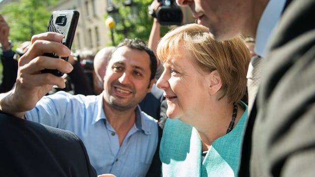 Angela Merkel macht mit einem Flüchtling ein Selfie.