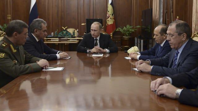 Putin sitzt am Kopf eines Tisches, mehrere Männer in Anzug oder Uniform sitzen links und rechts von ihm.
