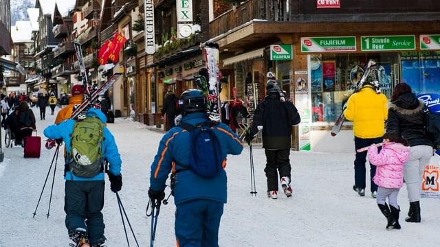 Symbolbild: Touristen zu Fuss unterwegs in Zermatt, viele tragen ihre Ski auf den Schultern.
