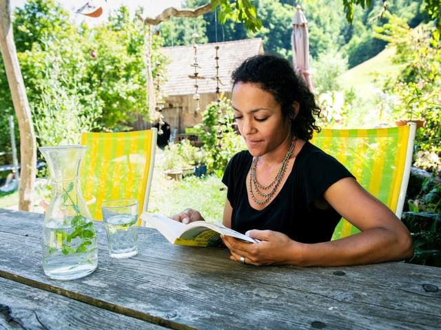 Eine Frau sitzt an einem Tisch und liest ein Buch.