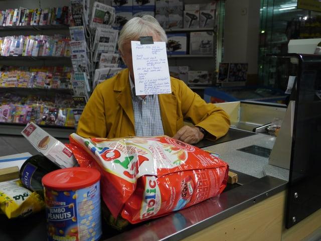 Emil Steinberger sitzt an einer Supermarktkasse und hat ein Blatt Papier an die Stirn geklebt.