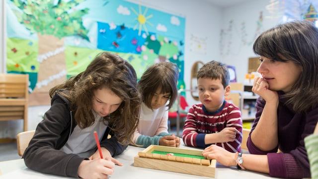 Drei Kinder sitzen neben ihrer Kindergärtnerin und zeichnen.