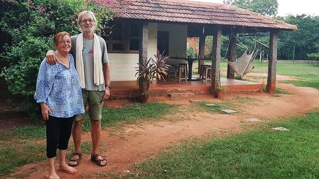 Zwei Menschen stehen vor einem Haus.